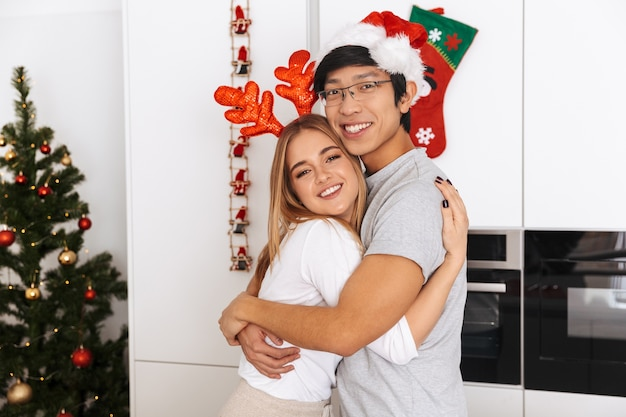 Lindo casal, homem e mulher vestindo roupas de natal, em pé na cozinha bem iluminada e se abraçando