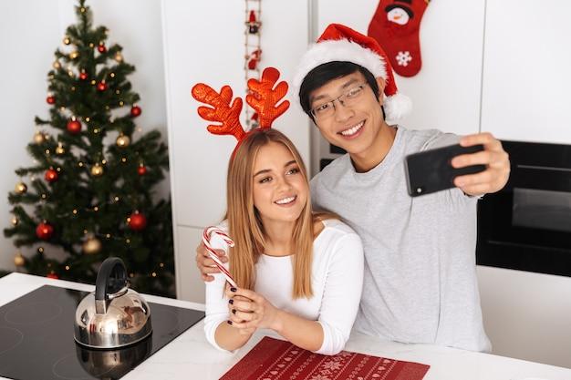 Lindo casal, homem e mulher vestindo roupas de natal, em pé na cozinha bem iluminada e tirando uma foto de selfie no celular