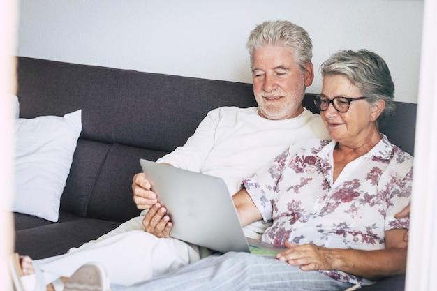 Lindo casal idoso caucasiano em casa assistindo a um filme ou pesquisando na web, sentado no sofá com um laptop nas pernas