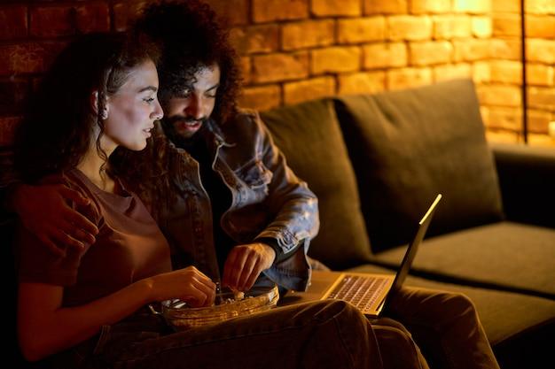 Lindo casal inter-racial passa os fins de semana juntos, assistindo a um filme no laptop em casa, comendo pipoca. homem e mulher atraentes se divertindo, em trajes casuais domésticos