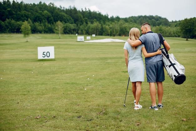 Lindo casal jogando golfe em um campo de golfe
