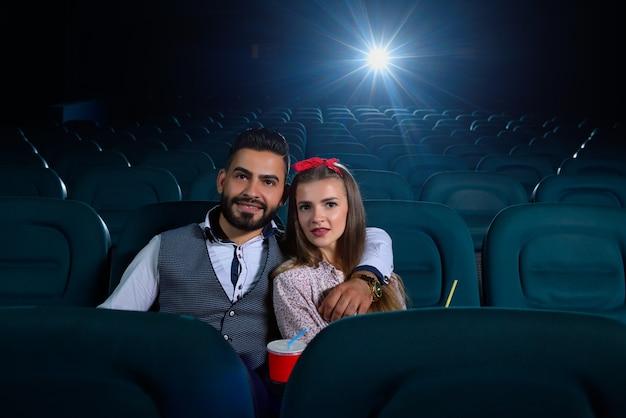 Lindo casal jovem abraçando enquanto assiste a um filme em uma sala de cinema vazia copyspace