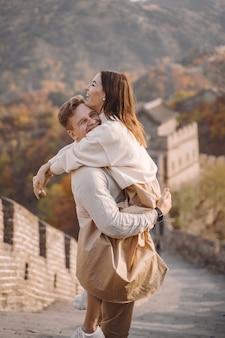 Lindo casal jovem abraçando na grande muralha da china