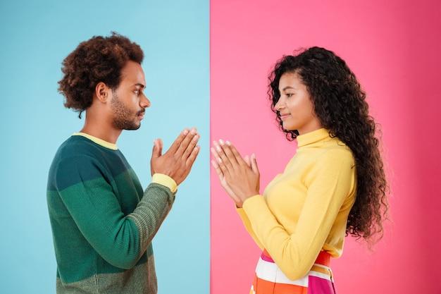 Lindo casal jovem africano em pé com as mãos postas sobre um fundo azul e rosa