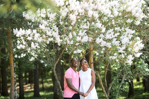 Lindo casal jovem africano no parque florido de verão