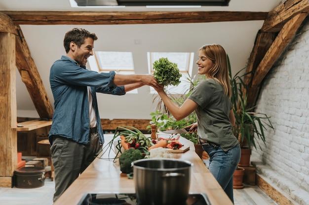 Lindo casal jovem alegre cozinhar jantar juntos