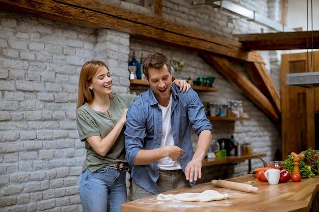 Lindo casal jovem alegre, preparando o jantar juntos e se divertindo na cozinha rústica