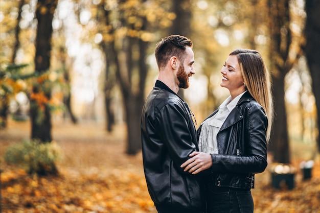Lindo casal jovem andando no parque outono em um dia ensolarado