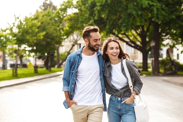 Lindo casal jovem apaixonado caminhando ao ar livre na rua da cidade, se abraçando