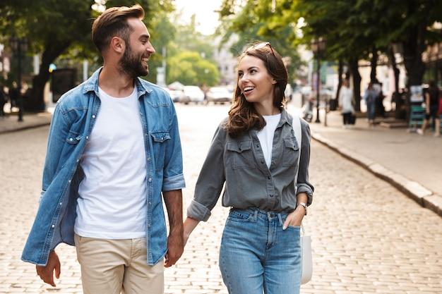 Lindo casal jovem apaixonado caminhando ao ar livre na rua da cidade