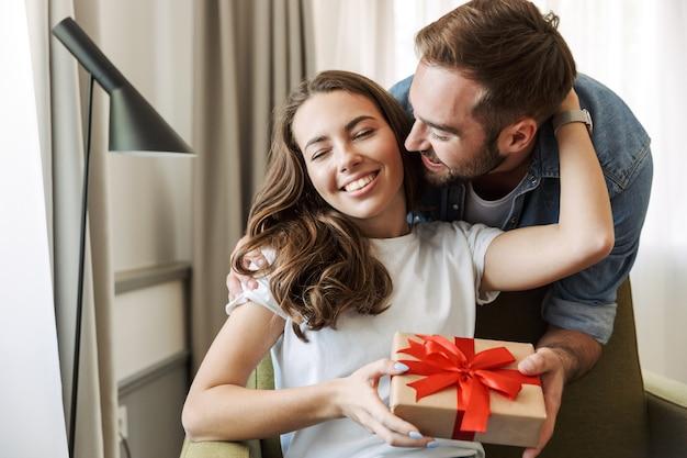 Lindo casal jovem apaixonado em casa, comemorando com uma troca de caixa de presente, se abraçando