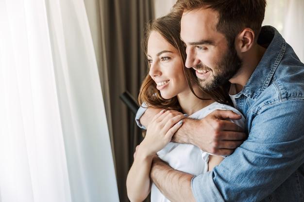 Lindo casal jovem apaixonado em casa, em pé na janela, se abraçando