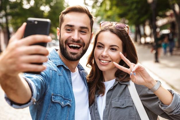 Lindo casal jovem apaixonado em pé ao ar livre na rua da cidade, tirando uma selfie, mostrando um gesto de paz