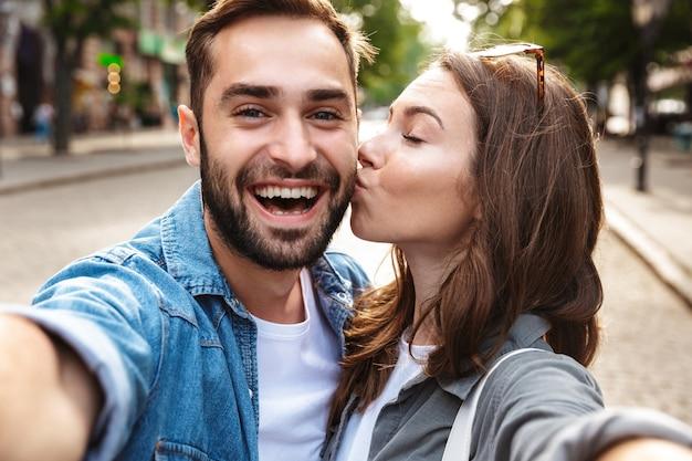 Lindo casal jovem apaixonado em pé ao ar livre na rua da cidade, tirando uma selfie, se beijando