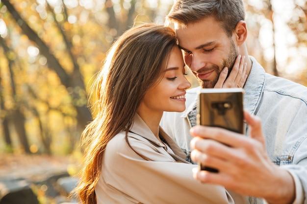 Lindo casal jovem apaixonado usando telefone celular enquanto passa um tempo no parque de outono, tirando uma selfie