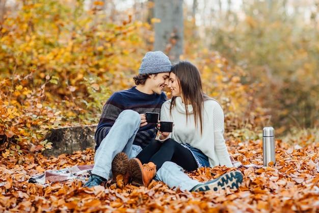 Lindo casal jovem aproveitando a hora do piquenique na floresta