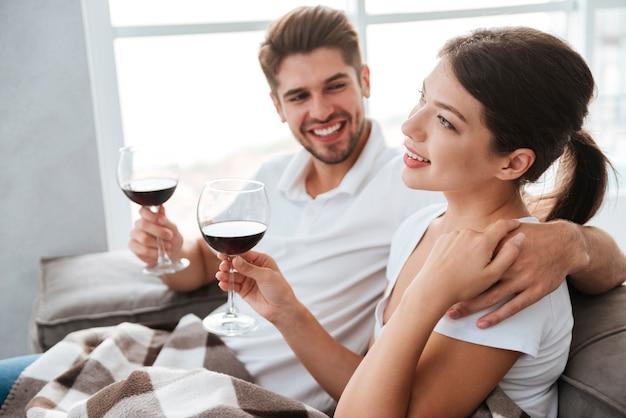 Lindo casal jovem bebendo vinho tinto em casa juntos