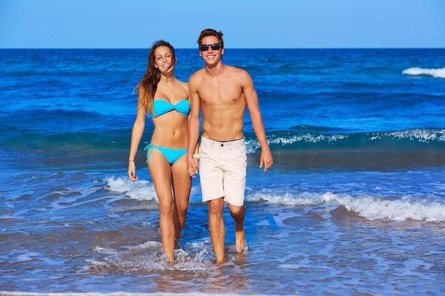 Lindo casal jovem caminhando na praia
