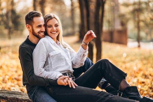 Lindo casal jovem caminhando no parque de outono em um dia ensolarado