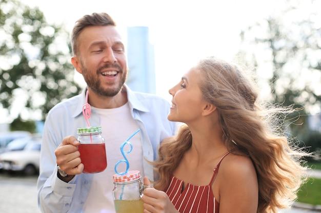 Lindo casal jovem caminhando pela rua da cidade, sorrindo e bebendo coquetéis frescos.