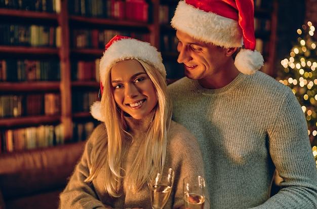 Lindo casal jovem com chapéus de papai noel está segurando taças de champanhe e sorrindo enquanto celebra o ano novo em casa. no contexto da árvore de natal.