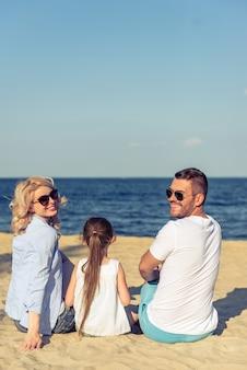 Lindo casal jovem com filha na praia.