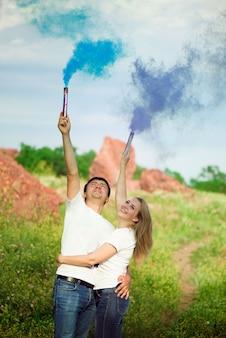 Lindo casal jovem com fumaça colorida nas mãos.