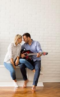 Lindo casal jovem com guitarra no quarto