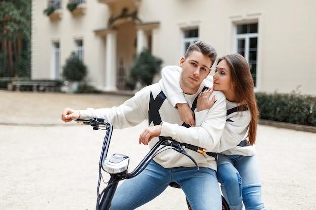 Lindo casal jovem com roupas da moda anda de bicicleta