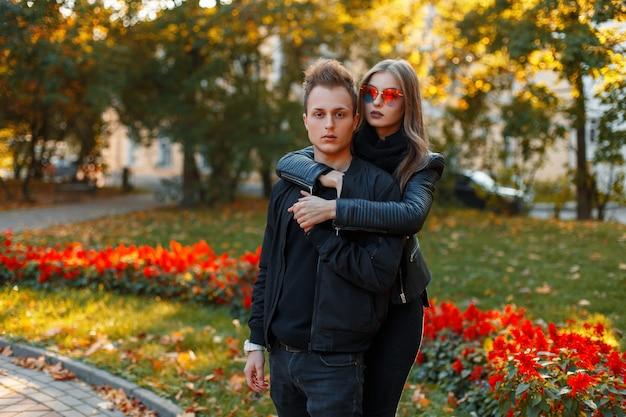 Lindo casal jovem com roupas pretas elegantes, dia de outono no parque