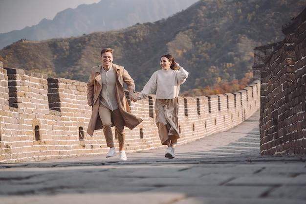 Lindo casal jovem correndo e pulando na grande muralha da china.
