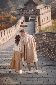 Lindo casal jovem de mãos dadas e mostrando carinho na grande muralha da china.