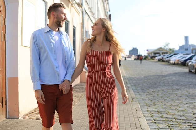Lindo casal jovem de mãos dadas e sorrindo enquanto caminhava pela rua da cidade.