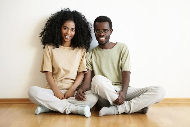 Lindo casal jovem de pele escura casual sentado no chão de madeira depois de se mudar para um novo apartamento