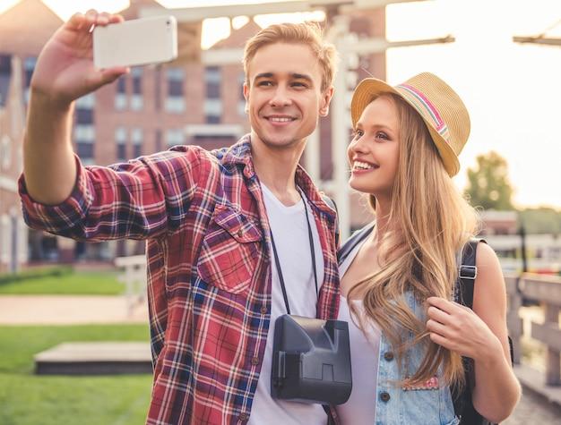 Lindo casal jovem de viajantes está fazendo selfie.