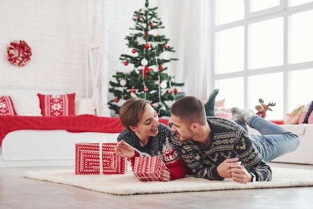Lindo casal jovem deitado na sala de estar com árvore verde férias