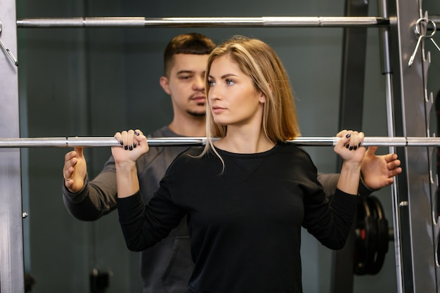 Lindo casal jovem desportivo fazendo exercícios no ginásio. conceito de estilo de vida saudável