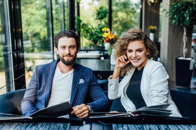 Lindo casal jovem e bonito com cardápio em um restaurante fazendo pedidos