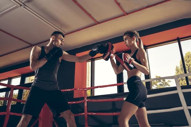 Lindo casal jovem e esportivo malhando na academia juntos