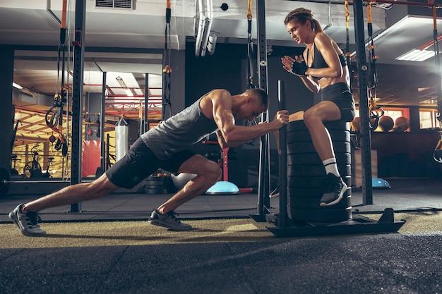 Lindo casal jovem e esportivo treinando na academia juntos