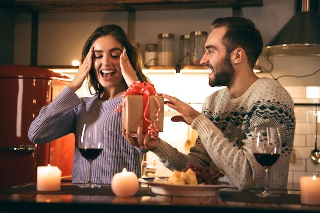 Lindo casal jovem e feliz passando uma noite romântica juntos em casa, bebendo vinho tinto e um homem dando um presente