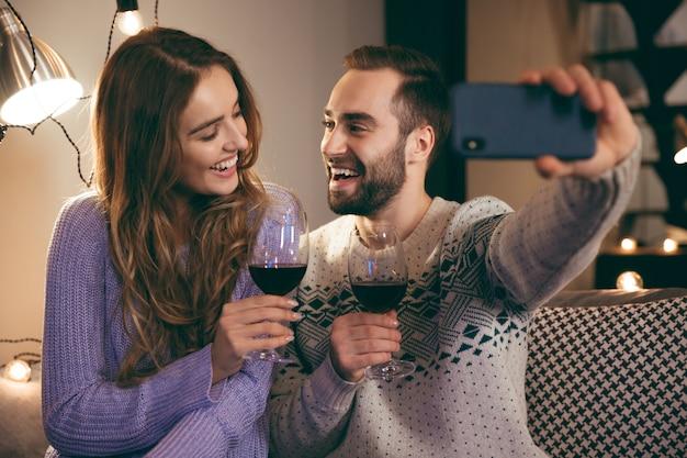Lindo casal jovem e feliz passando uma noite romântica juntos em casa, bebendo vinho tinto, tirando uma selfie