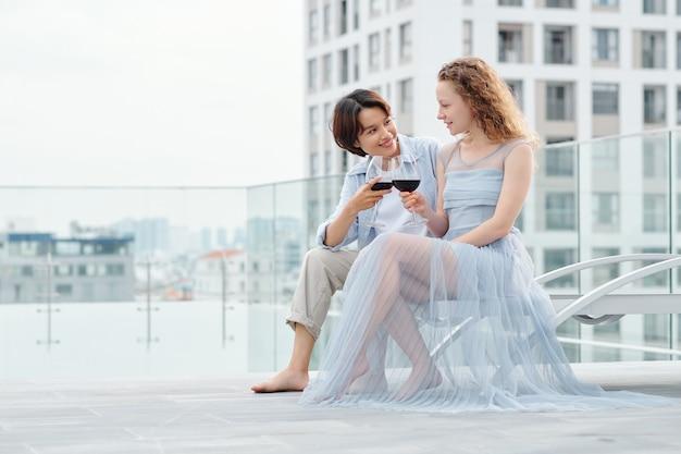 Lindo casal jovem e multiétnico de lésbicas bebendo vinho e conversando no telhado