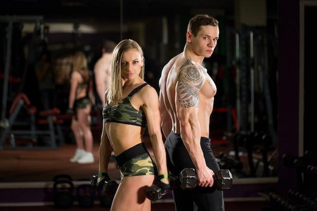 Lindo casal jovem e sexy desportivo mostrando músculos e treino na academia