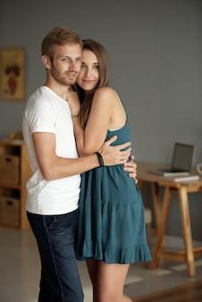 Lindo casal jovem e sorridente apaixonado se abraçando e olhando pela janela do apartamento