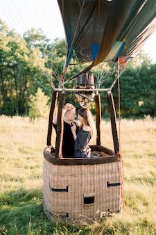 Lindo casal jovem e sorridente apaixonado, vestindo roupas pretas casuais, ficando e se abraçando na cesta de balão de ar ao pôr do sol, pronto para seu primeiro voo de balão