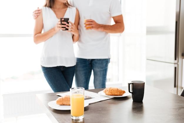 Lindo casal jovem em frente à mesa com café da manhã na cozinha