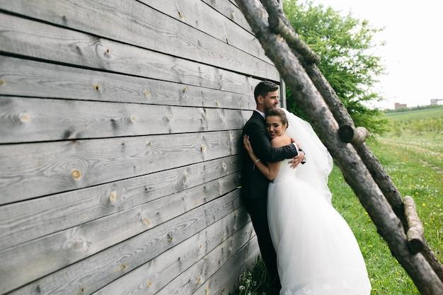 Lindo casal jovem em pé perto da velha casa de madeira