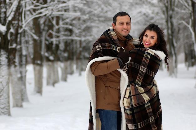 Lindo casal jovem em um parque coberto de neve envolto em uma manta quente caminha