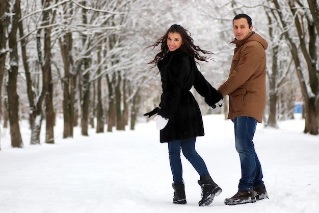 Lindo casal jovem em um parque nevado envolto em uma manta quente caminha